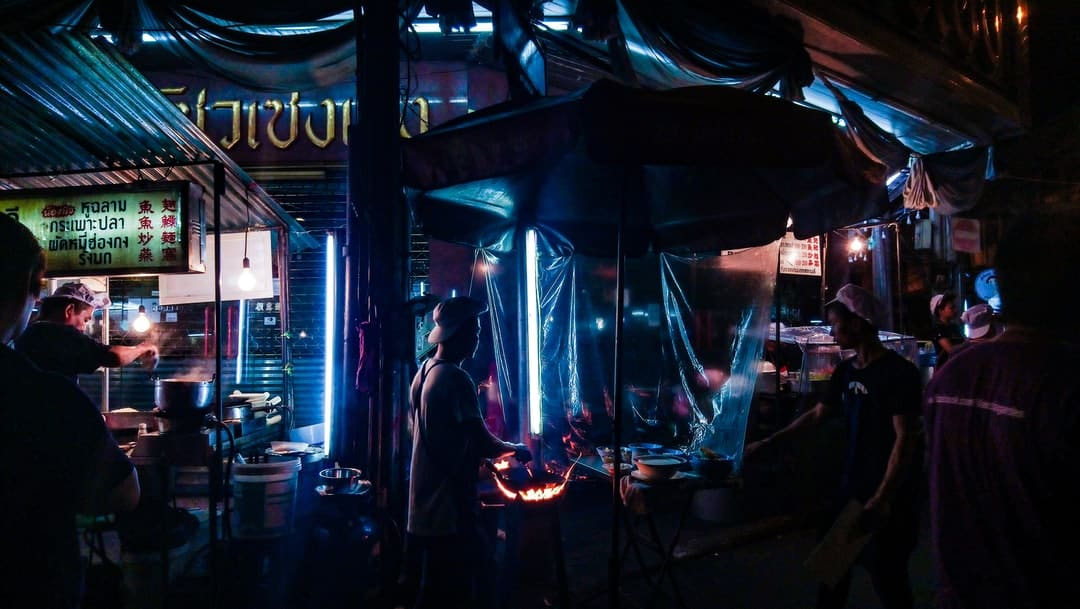 A group of people standing in front of a store front at night